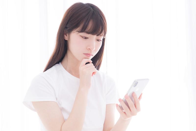 携帯を持って悩む女性