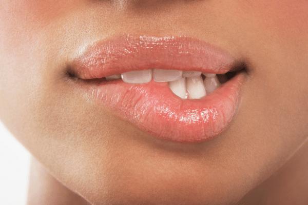 前歯で唇を噛む