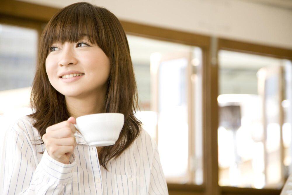ティーカップを片手に微笑む女性