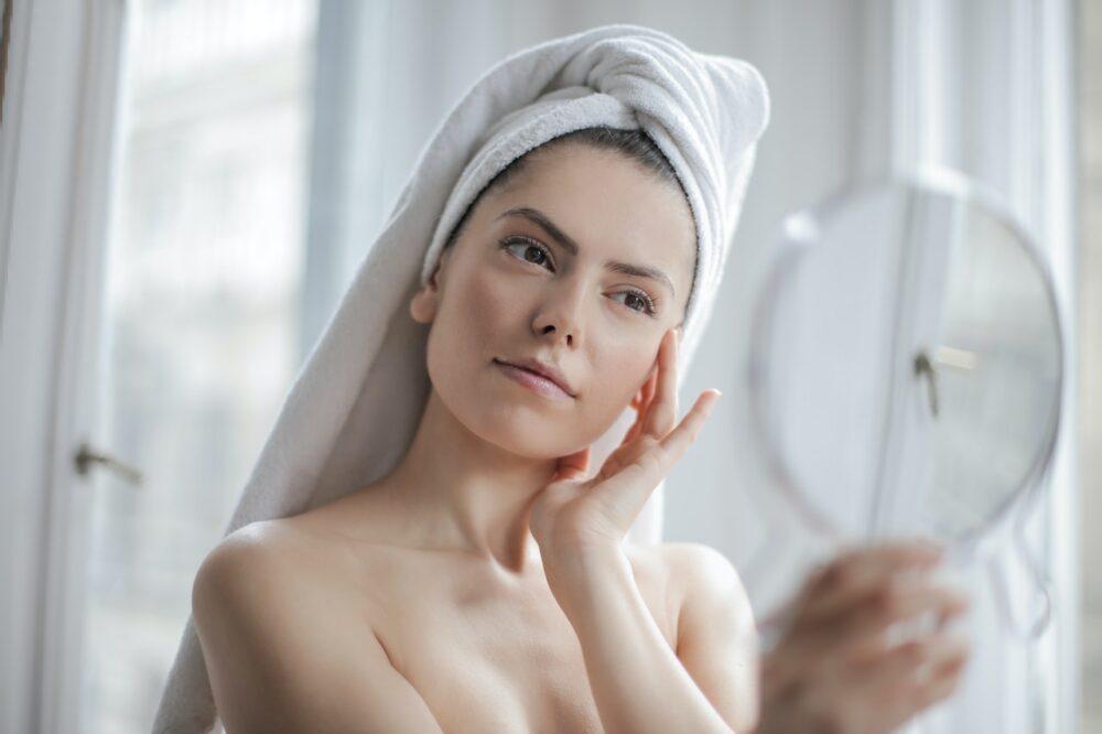 鏡を見て首をかしげる女性